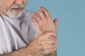Homem sentindo dor por causa de artrite reumatoide