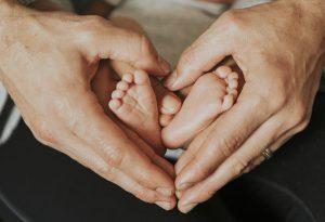 Pai segura os pés de seu bebê por causa de Programa Empresa Cidadã